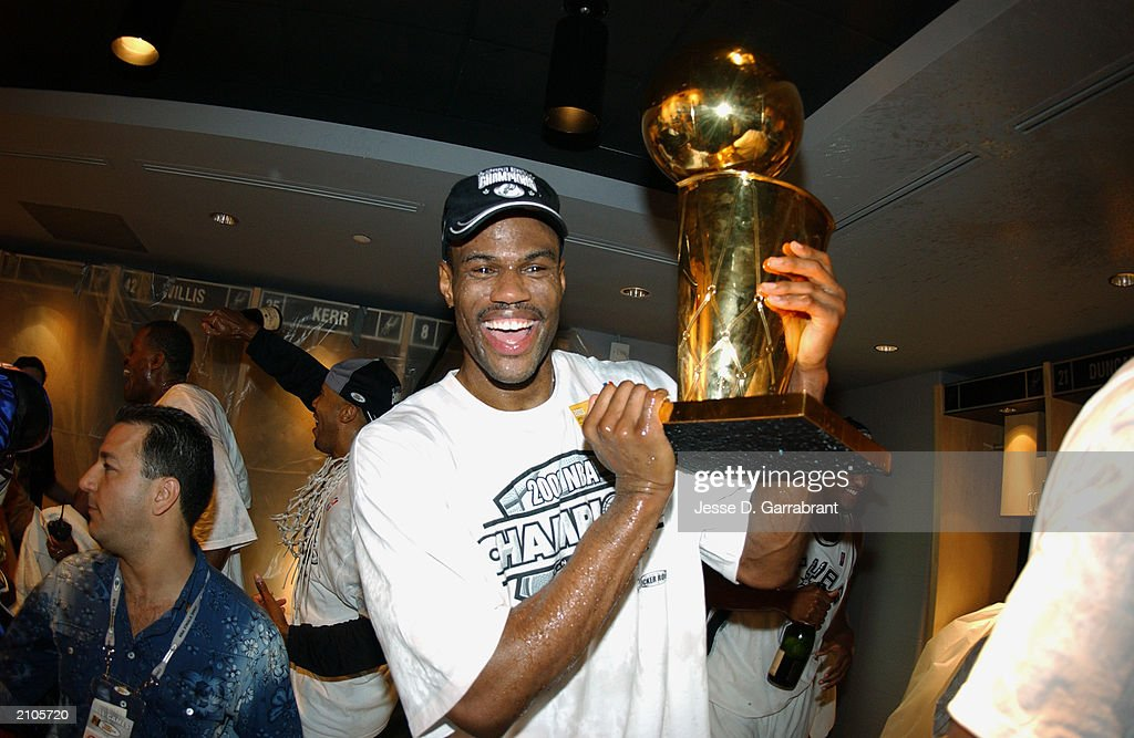 David Robinson #50 of the San Antonio Spurs poses with the NBA Championship trophy in Game six of the 2003 NBA Finals against the New Jersey Nets at SBC Center on June 15, 2003 in San Antonio, Texas. The Spurs won 88-77 and defeated the Nets to win the NBA Championship.