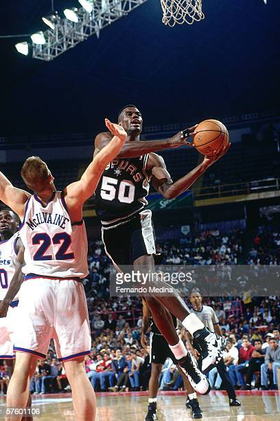 David Robinson of the San Antonio Spurs shoots against Jim McIlvaine of the Washington Bullets during the 1995 Mexico Challenge on October 28, 1995...