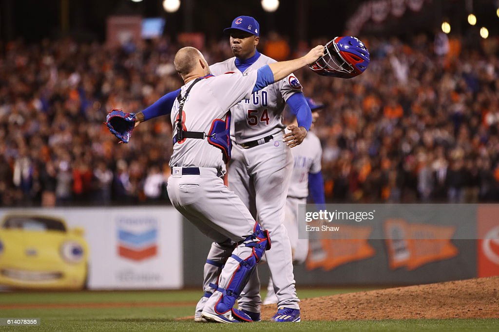 David Ross #3 and Aroldis Chapman #54 of the Chicago Cubs celebrate after defeating the San Francisco Giants 6-5 in Game Four of their National League Division Series to advance to the National League Championship Series at AT&T Park on October 11, 2016 in San Francisco, California.
