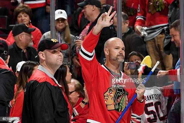David Ross former MLB catcher and World Series winner with the Chicago Cubs waves to the crowd after shooting the puck in between periods of the game...
