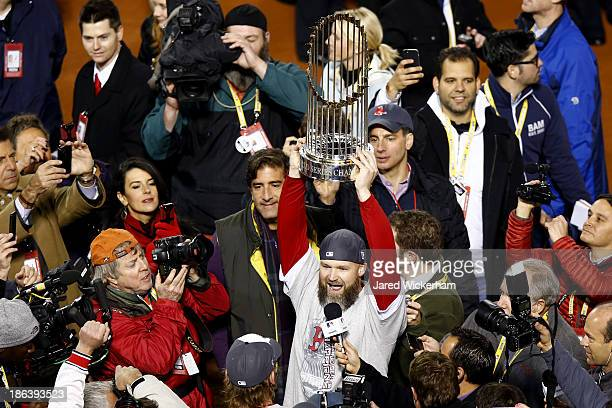 David Ross of the Boston Red Sox holds up the World Series trophy after defeating the St Louis Cardinals 61 in Game Six of the 2013 World Series at...