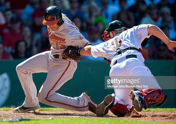 David Ross of the Boston Red Sox tags out Manny Machado of the Baltimore Orioles in the seventh inning at Fenway Park on July 6 2014 in Boston...