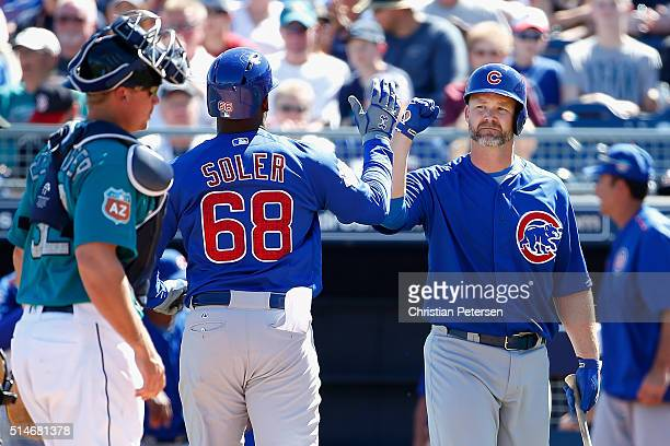David Ross of the Chicago Cubs highfives Jorge Soler after Soler hit a solo home run against the Seattle Mariners during the second inning of the...