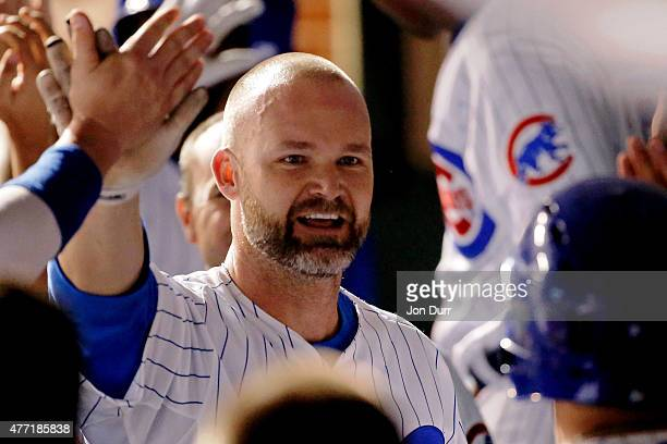 David Ross of the Chicago Cubs is congratluated in the dugout after scoring against the Cincinnati Reds during the seventh inning at Wrigley Field on...