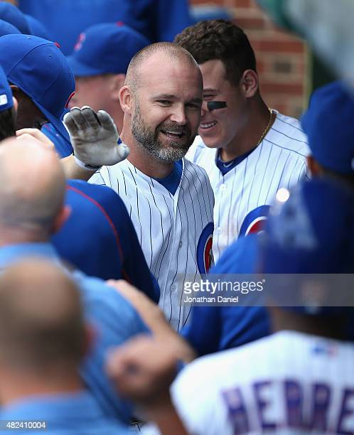 David Ross of the Chicago Cubs is greeted in the dugout after hitting a home run in the bottom of the 9th inning against the Philadelphia Phillies at...