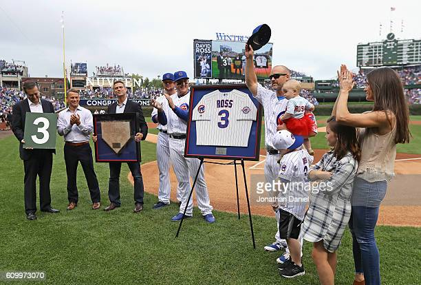 David Ross of the Chicago Cubs standing with his family and who is retiring after the season tips his hat to the crowd as he is honored by Cubs...