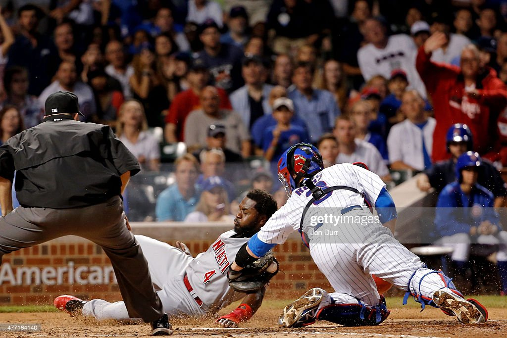 David Ross #3 of the Chicago Cubs tags out Brandon Phillips #4 of the Cincinnati Reds at home plate during the sixth inning at Wrigley Field on June 14, 2015 in Chicago, Illinois.