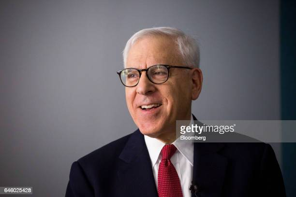 David Rubenstein cochief executive officer of the Carlyle Group LP smiles backstage before an interview with James Gorman chief executive officer of...