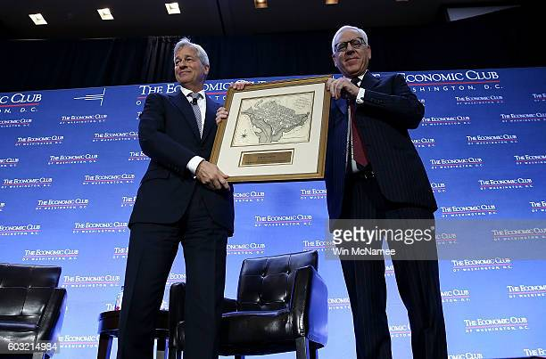 David Rubenstein cofounder of the Carlyle Group and President of the Economic Club of Washington presents a gift to Jamie Dimon chairman and CEO of...