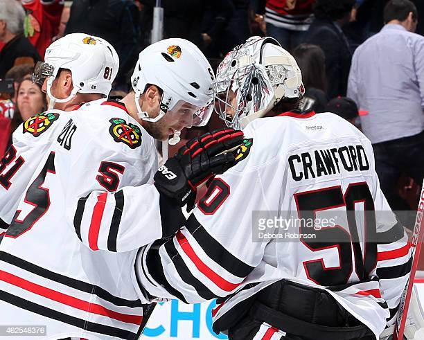 David Rundblad and Corey Crawford of the Chicago Blackhawks celebrate the Blackhawks' 41 win against the Anaheim Ducks on January 30 2015 at Honda...