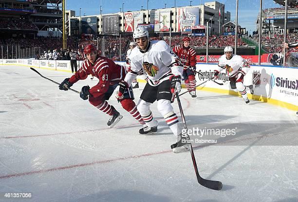 David Rundblad of the Chicago Blackhawks and Jay Beagle of the Washington Capitals pursue the play near the corner boards during the 2015 Bridgestone...