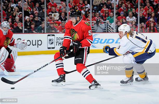 David Rundblad of the Chicago Blackhawks approaches the puck as Olli Jokinen of the Nashville Predators follows behind during the NHL game at the...