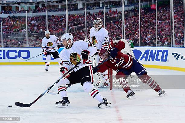 David Rundblad of the Chicago Blackhawks attempt to clear as Troy Brouwer of the Washington Capitals backchecks during the third period of the 2015...