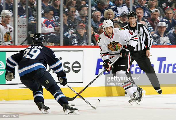 David Rundblad of the Chicago Blackhawks plays the puck up the ice as Toby Enstrom of the Winnipeg Jets defends during first period action at the MTS...