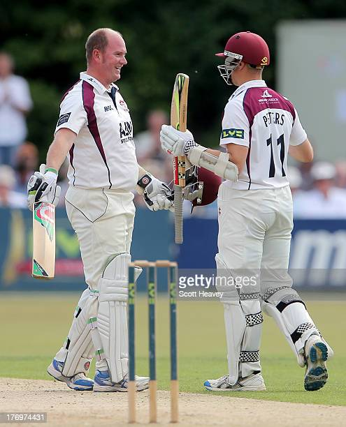 David Sales of Northampton celebrates reaching his century with Stephen Peters during day one of the LV County Championship Division Two game between...