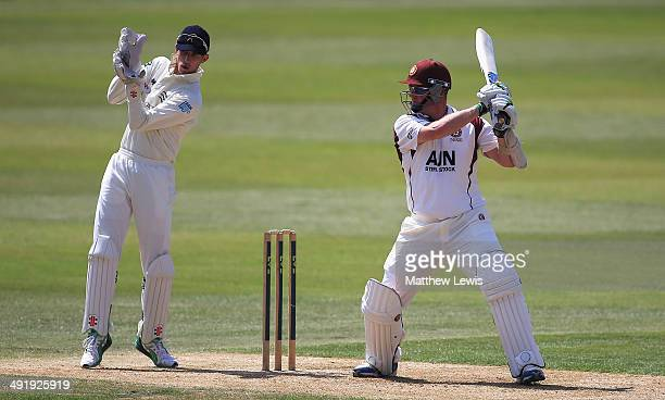 David Sales of Northamptonshire hits the ball towards the boundary as John Simpson of Middlesex looks on during the LV County Championship match...