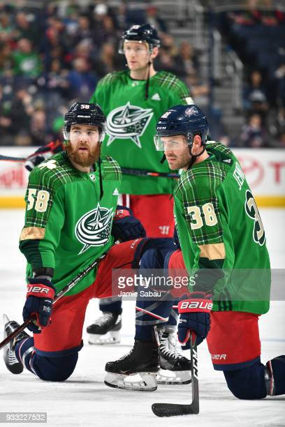David Savard Mark Letestu and Boone Jenner all of the Columbus Blue Jackets wear special green jerseys for St Patrick's Day during warm ups before a...