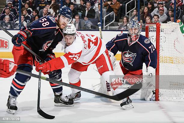 David Savard of the Columbus Blue Jackets and Cory Emmerton of the Detroit Red Wings battle for position in front of goaltender Sergei Bobrovsky of...