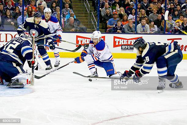 David Savard of the Columbus Blue Jackets attempts to block a shot by Drake Caggiula of the Edmonton Oilers as Sergei Bobrovsky of the Columbus Blue...