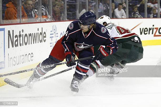 David Savard of the Columbus Blue Jackets chases the puck in the corner against Guillaume Latendresse of the Minnesota Wild during their game on...