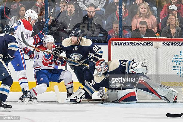 David Savard of the Columbus Blue Jackets checks Brendan Gallagher of the Montreal Canadiens in front of goaltender Sergei Bobrovsky of the Columbus...