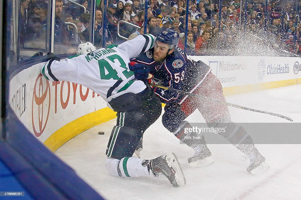 David Savard #58 of the Columbus Blue Jackets checks Valeri Nichushkin #43 of the Dallas Stars into the boards while chasing after the puck during the third period on March 4, 2014 at Nationwide Arena in Columbus, Ohio. Columbus defeated Dallas 4-2.