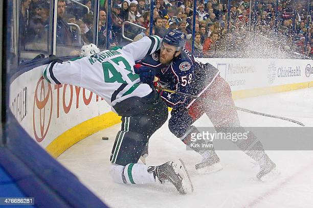 David Savard of the Columbus Blue Jackets checks Valeri Nichushkin of the Dallas Stars into the boards while chasing after the puck during the third...