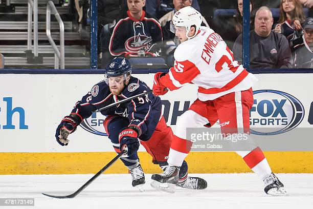 David Savard of the Columbus Blue Jackets defends against Cory Emmerton of the Detroit Red Wings on March 11 2014 at Nationwide Arena in Columbus Ohio