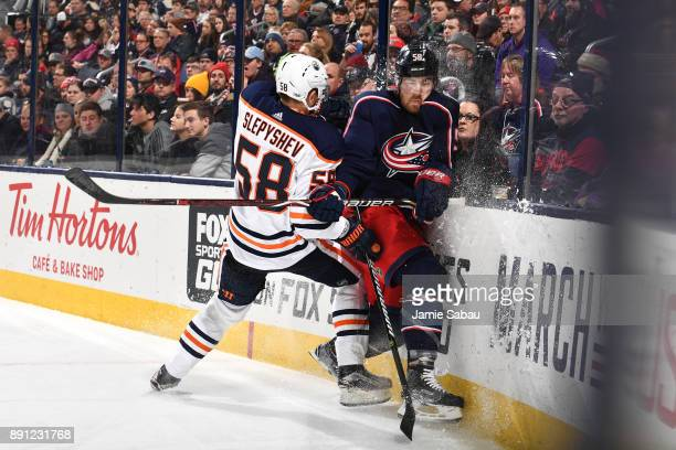 David Savard of the Columbus Blue Jackets is checked into the boards by Anton Slepyshev of the Edmonton Oilers during the second period of a game on...