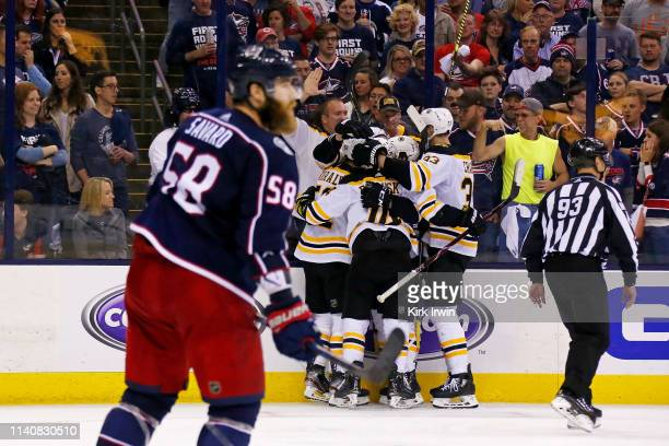 David Savard of the Columbus Blue Jackets skates off of the ice as Sean Kuraly of the Boston Bruins is congratulated by his teammates after scoring a...