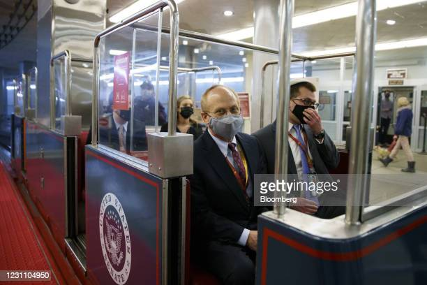 David Schoen, defense attorney for Donald Trump, center, wears a protective mask while riding the Senate Subway at the U.S. Capitol in Washington,...