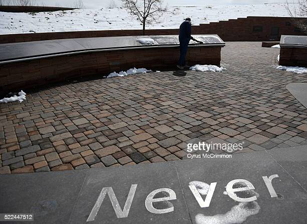 David Settle from Bowling Green Kentucky sweeps the snow off the memorials to the victims at the Columbine Memorial in Clement Park in Littleton...
