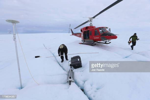 David Shean a PhD student at the University of Washington and Scientist Ian Joughin of the University of Washington place a GPS system into the ice...
