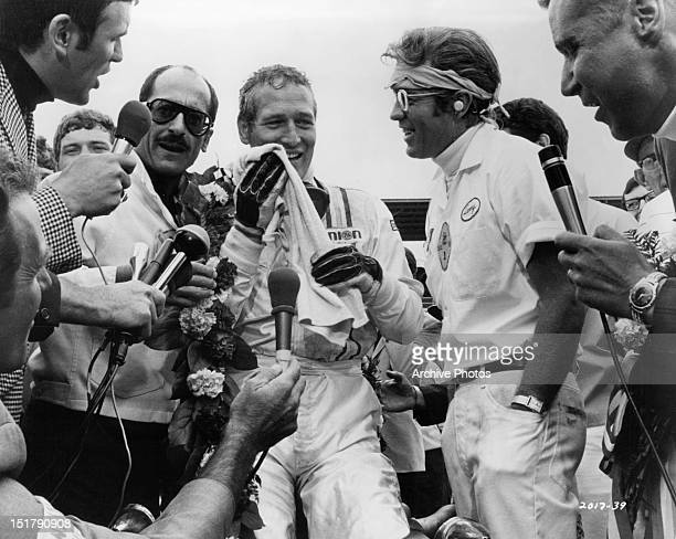 David Sheiner Paul Newman Clu Gulager and another man in the winner's circle after the race in a scene from the film 'Winning' 1969