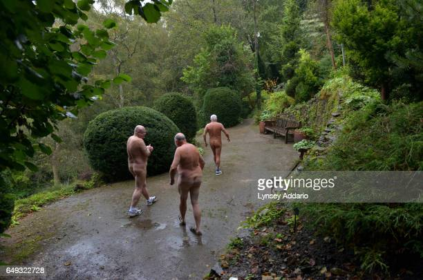 David Shelly left Ron Law center and Barry Graanop walk along with other naturists on Clothes Optional Day in the Abbey House Gardens in Malmesbury...