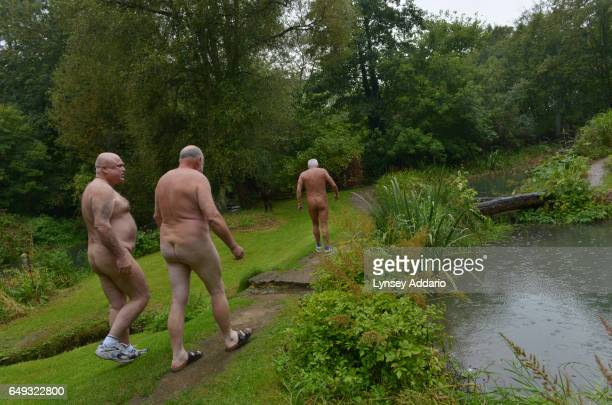 David Shelly left Ron Law center and Barry Graanop walk with other naturists on Clothes Optional Day in the Abbey House Gardens in Malmesbury England...