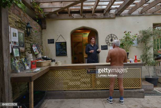 David Shelly speaks with the waitress as he gathers with other naturists on Clothes Optional Day in the Abbey House Gardens in Malmesbury England...