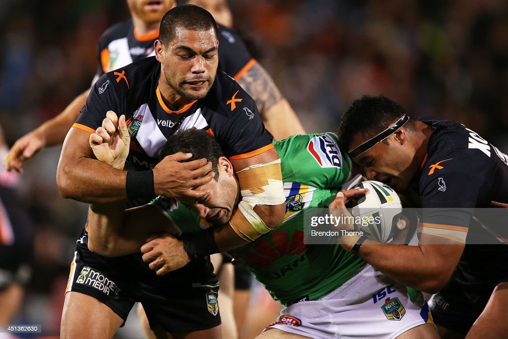 David Shillington of the Raiders is tackled by Adam Blair and Ava Seumanufagai of the Tigers during the round 16 NRL match between the Wests Tigers and the Canberra Raiders at Campbelltown Sports Stadium on June 28, 2014 in Sydney, Australia.
