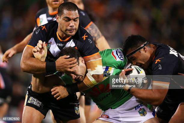 David Shillington of the Raiders is tackled by Adam Blair and Ava Seumanufagai of the Tigers during the round 16 NRL match between the Wests Tigers...