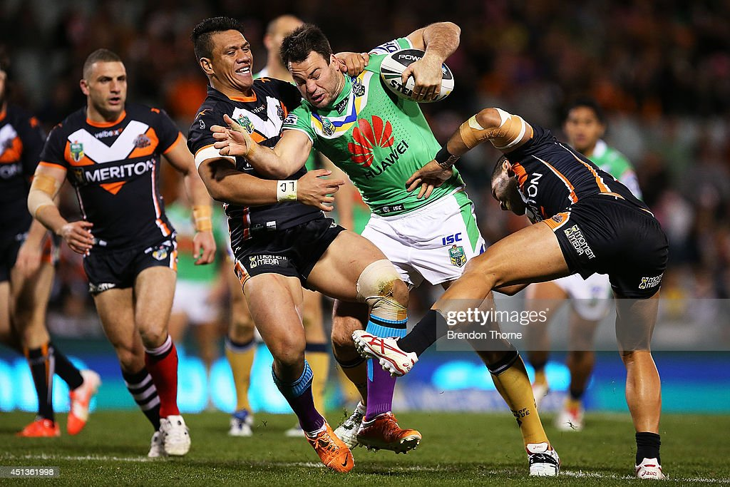 David Shillington of the Raiders is tackled by Sauaso Sue and Adam Blair of the Tigers during the round 16 NRL match between the Wests Tigers and the Canberra Raiders at Campbelltown Sports Stadium on June 28, 2014 in Sydney, Australia.