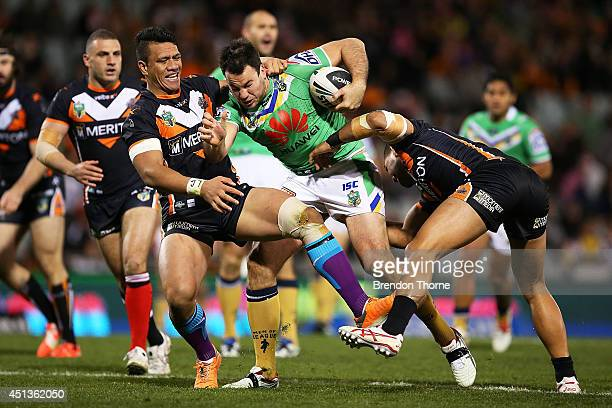 David Shillington of the Raiders is tackled by Sauaso Sue and Adam Blair of the Tigers during the round 16 NRL match between the Wests Tigers and the...