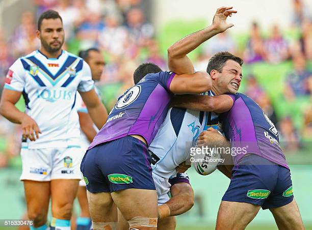 David Shillington of the Titans is tackled by Jordan McLean and Cameron Smith of the Storm during the round two NRL match between the Melbourne Storm...