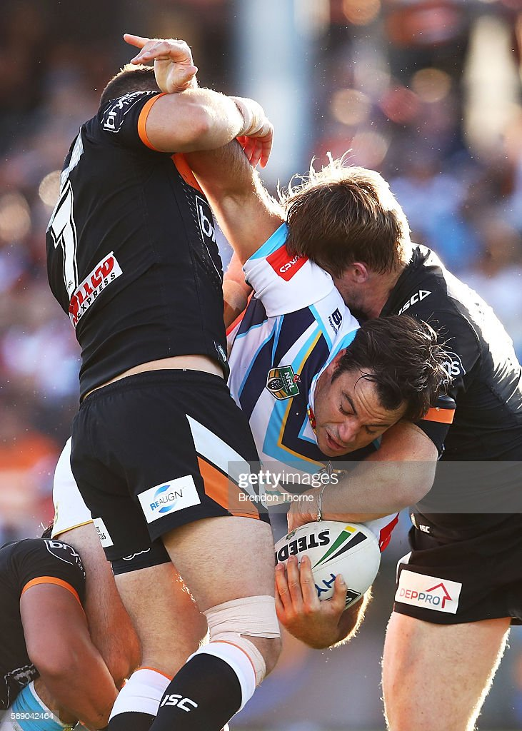 David Shillington of the Titans is tackled by the Tigers defence during the round 23 NRL match between the Wests Tigers and the Gold Coast Titans at Campbelltown Sports Stadium on August 13, 2016 in Sydney, Australia.