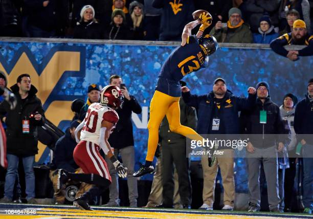 David Sills V of the West Virginia Mountaineers catches a 10 yard touchdown pass in the first half against Robert Barnes of the Oklahoma Sooners on...