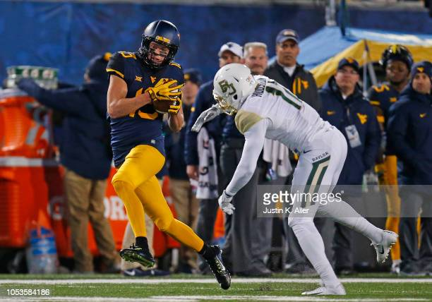 David Sills V of the West Virginia Mountaineers catches a 65 yard touchdown pass in the first half against Jameson Houston of the Baylor Bears at...