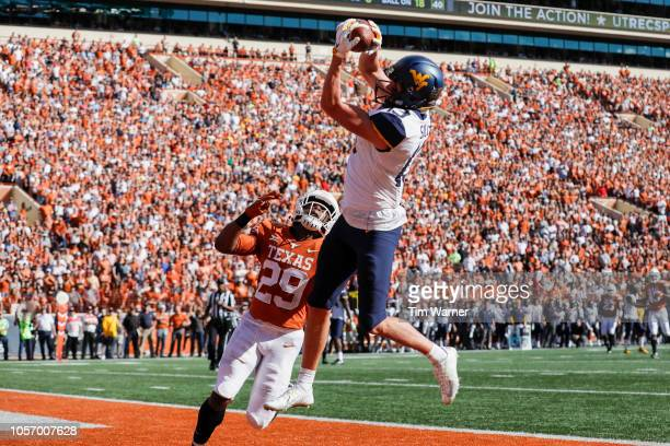 David Sills V of the West Virginia Mountaineers catches a pass for a touchdown defended by Josh Thompson of the Texas Longhorns in the second quarter...