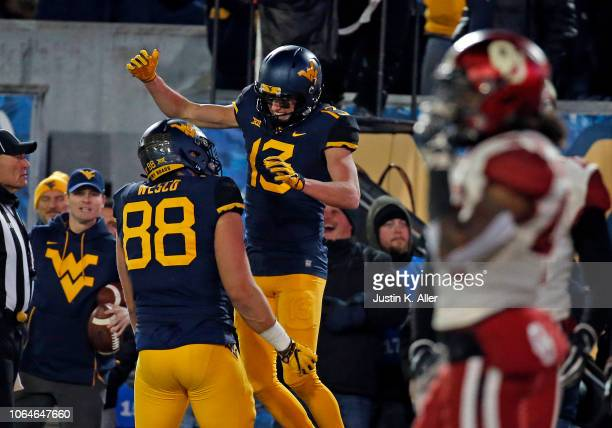 David Sills V of the West Virginia Mountaineers celebrates after catching a 10 yard touchdown pass in the first half against Robert Barnes of the...