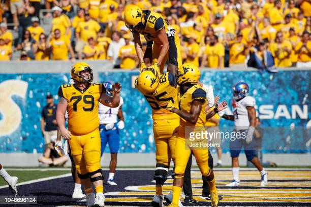 David Sills V of the West Virginia Mountaineers is lifted up by Isaiah Hardy after catching a 17yard touchdown pass against the Kansas Jayhawks in...