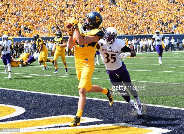 David Sills V of the West Virginia Mountaineers makes a touchdown catch in front of Chris Love of the East Carolina Pirates during the second quarter...
