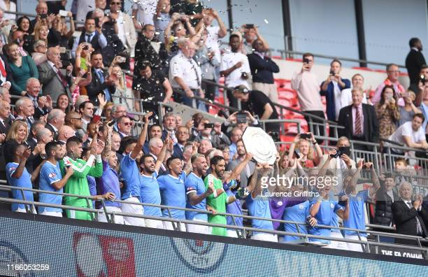 David Silva and Sergio Aguero of Manchester City lift the FA Community Shield following their team's victory in the FA Community Shield match between...